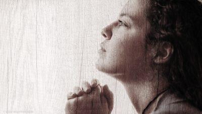 Eine Frau, im Gebet versunken, schaut nach oben. Über das ganze Bild ist ein Filter gelegt, der stark an rauhes Holz erinnert.