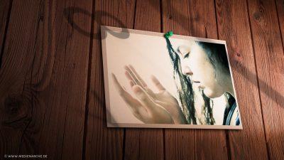 Das Bild einer betenden Frau, das an eine Holzwand gepinnt ist, durch Schattenzahlen leicht angedeutet kann man eine Uhr erahnen.