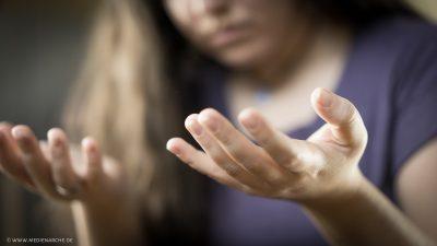 Eine im Gebet versunkene Frau, die ihre leeren Hände zum Empfangen ausstreckt.