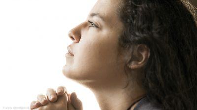 Eine Frau, im Gebet versunken, schaut nach oben.