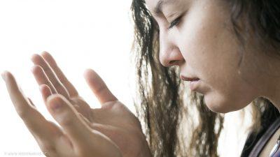 Eine betende Frau, die ihre Hände flehend auf Höhe ihres Gesichts ausstreckt.
