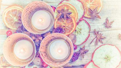 Nahaufnahme einer Adventsdekoration mit Teelichtern, Orangenscheiben, Sternanis, HImbeeren, Zimtstangen, Apfelscheiben und Nüssen und roten Beeren