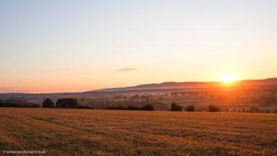 Eine noch in Frühnebel getauchte Landschaft, mit einem strahlenden Sonnenaufgang.
