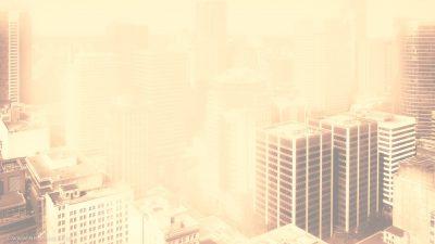 Aufnahme eines Häuserblocks in einer Großstadt. Im Hintergrund sind die Wolkenkratzer der Downtown erkennbar.