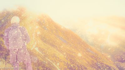 Ein Wanderer steht vor einem massiven Berg, an dessen Grat sich ein Pfad zur Spitze heraufschlängelt.
