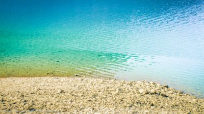 Blick ins Wasser an einem Seeufer mit einem Steinstrand
