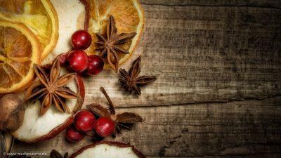 Nahaufnahme einer Adventsdekoration mit Apfelscheiben, Orangenscheiben, Sternanis und roten Beeren, auf einer Holzunterlage
