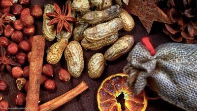 Lose Erdnüsse und Haselnüsse zwischen denen Zimtstangen und Sternanis liegen.
