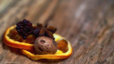 Nahaufnahme einer Adventsdekoration mit Orangenscheiben, Sternanis, HImbeere und Nuss