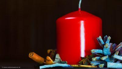 Eine große rote Kerze in einem Adventsgesteck mit Zimtstange, Tannenzapfen, Sternen, Sternanis und Holzelementen, vor einem dunklen Hintergrund.