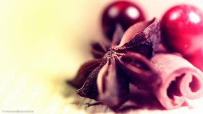 Nahaufnahme einer Adventsdekoration mit Sternanis, Zimtstangen und roten Beeren