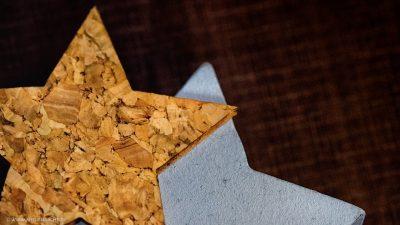 Ein Stern aus Kork und ein weisser, die aufeinander auf einem dunklen Hintergrund liegen.