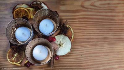 Von oben fotografiertes kleines Arrengement mit drei Teelichtern in Haltern, umgeben von getrockneten Apfel- und Orangenscheiben, Zimtstangen, Sternanis, roten Beeren und Nüssen.