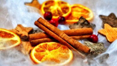 Zimtstangen, getrocknete Orangenscheiben, rote Beeren und Sterne aus Holzrinde auf weißem Engelshaar.
