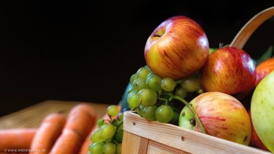 Schöne, glänzende Äpfel in einem Korb mit weiterem Obst und Gemüse.