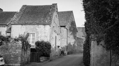 Ein altes romanisches Dorf mit aus Stein gemauerten Häusern. Schwarz-weiß Fotografie.