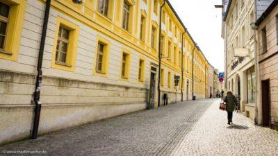 Eine Strasse in einer Altstadt. Historische Hausfassaden links und rechts, die in die Höhe ragen.