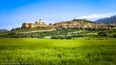 Eine antike meditterane Stadt auf einer Anhöhe, im Vordergrund ein saftig grünes Getreidefeld.