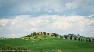 Ein auf einem grasgrünen Hügel gelegenes Anwesen.