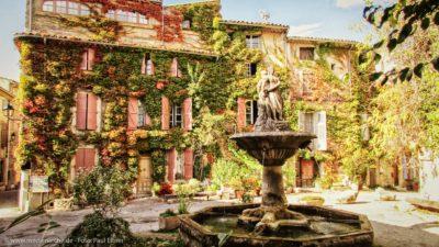 Ein altes Anwesen, dessen Wände fast vollständig von Efeuranken bewachsen sind. Im Vordergrund ein kunstvoller Brunnen.