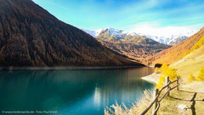 Ein azurblauer Bergsee im Herbst, gelbgefärbte Bäume am Ufer und schneebedeckte Berge im Hintergrund.