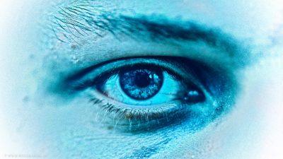 Großaufnahme von einem Auge, das den Betrachter hinter einem blauen Filter anschaut.