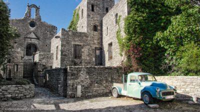 Ein Oldtimer vor einer Burg. Das blaue Auto bildet einen Kontrast zu den grauen Steinmauern der Burg.