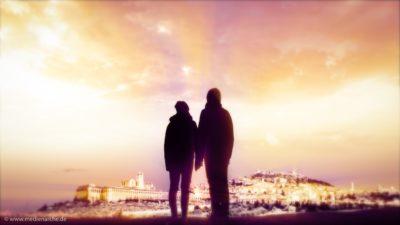 Zwei Menschen, die auf eine golden glänzende Stadt blicken.
