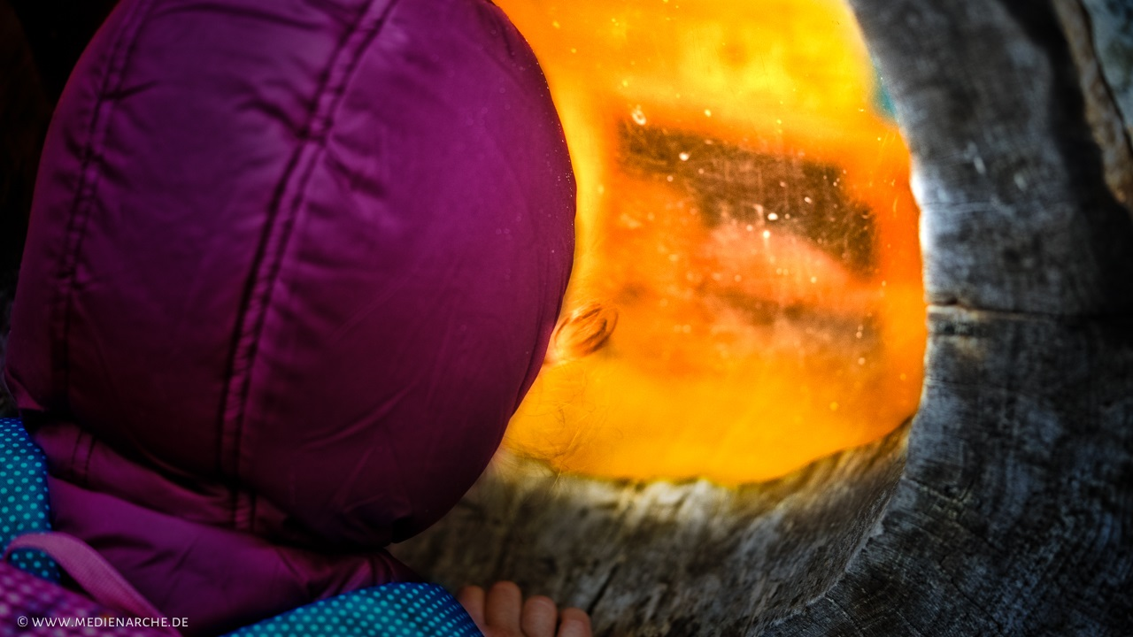 Ein kleines Kind, dass in der dunklen Kälte steht und sehnsuchtsvoll in ein warm erleuchtetes Fenster blickt.