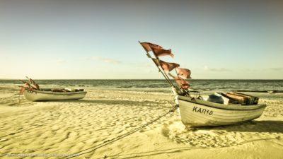 Zwei Boote auf einem Sandstrand.