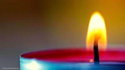 Ein brennendes rotes Teelicht, mit einer ruhigen, orangenen Flamme.