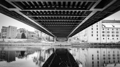 Unteransicht einer Brücke über einen ruhig dahinfließenden Fluss. Im Hintergrund historische Gebäude einer Stadt.