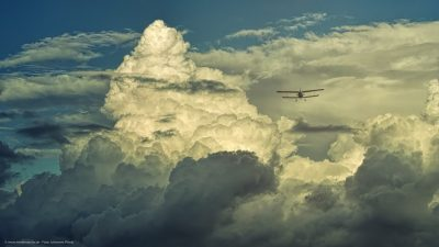 Ein Doppeldecker-Flugzeug über dramatisch aussehenden Cumulus-Wolken.