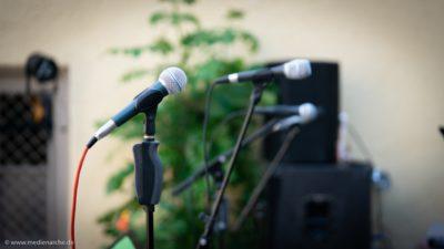 Eine Reihe von Mikrophonen auf einer Open-Air Bühne, kurz vor dem Konzert