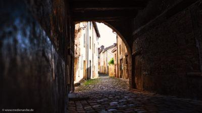Ein dunkler Durchgang mit Pflastersteinen, auf der anderen Seite eine kleine Gasse einer alten Siedlung