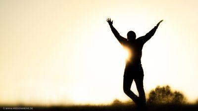 Eine Silhouette mit erhobenen Händen und wie im Sprung vor der untergehenden Sonne.