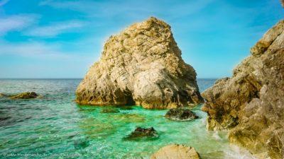Ein imposanter Felsbrocken im Meer, umgeben von smaragdgrünem Wasser.