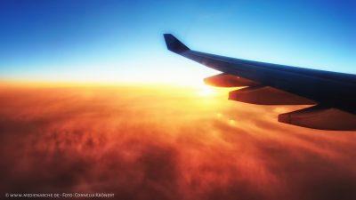 Blick aus einem Flugzeug auf einen strahlenden Sonnenaufgang der die Wolken erleuchtet. Im Vordergrund ein Flugzeugflügel.