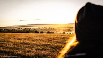 Ein strahlender Sonnenaufgang, im Vordergrund eine Frau.