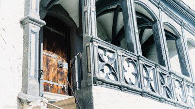 Treppenaufgang zu einer alten Holztür. Im Vordergrund ein Balkon mit kunstvollen Steinarbeiten.
