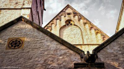 Spitze Giebel einer alten Kirche mit Verzierungen aus Stein, beleuchtet von der Abendsonne.