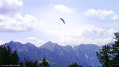 Ein Gleitschirm in luftigen Höhen, im Hintergrund eine Bergkette.