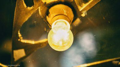 Leuchtende Glühbirne in einer schlichten, von Spiegeln umgebenen Fassung.