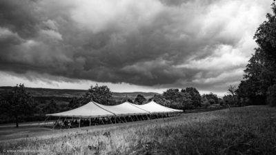 Ein großes Zelt, unter dem einige Menschen Unterschlupf vor einem aufziehenden Gewitter gefunden haben. Schwarz-weiß Fotografie.