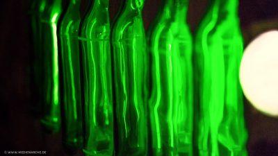 Eine Reihe von grünen Flaschen, die von einer Seite hell angestrahlt wird.