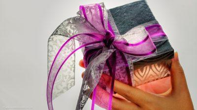 Ein paar Hände, das ein schön verpacktes und mit einer großen Schleife versehenes Geschenk darreicht.