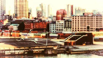 Eine alt aussehende Aufnahme eines Hafenbereichs und eines Güterbahnhofs vor der Skyline einer Großstadt.