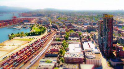 Blick auf eine Stadt und deren Handelsaktivitäten mit einem Güterbahnhof, Lastwagen und einem Hafen im Hintergrund. Miniatur-Effekt.