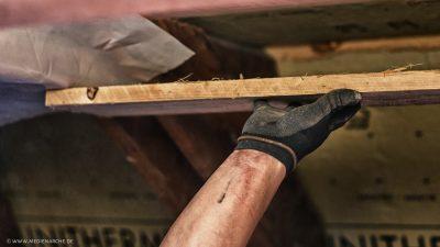 Ein Holzbrett, das während Bauarbeiten von einer Hand in die richtige Position gehalten wird bis es befestigt ist.