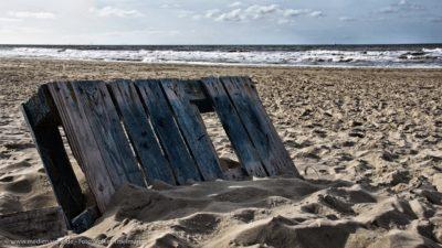 Ein Sandstrand, im Vordergrund eine halb mit Sand bedeckte alte Holzpalette.